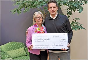 Martha Vetter, chief executive officer and founder of R/P Marketing Public Relations presents Sam Melden, executive director and chief thought officer of Food for Thought with a check.