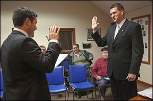 Wood County Commissioner Joel Kuhlman, left, swears in Walbridge Mayor Ed Kolanko on Wednesday at the first city council meeting of 2014. Four council members also took the oath of office.