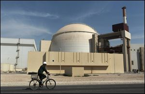 A worker rides a bicycle in front of the reactor building of the Bushehr nuclear power plant, just outside the southern city of Bushehr, Iran.
