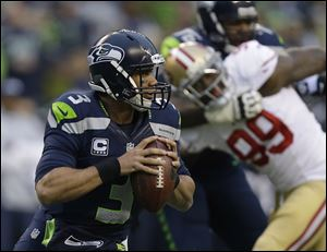 Seahawks quarterback Russell Wilson looks to pass during the first half on Sunday.