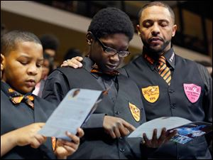 Dmarea Rankin, 10, left, Teryaon Perrin, 10, center, and  Toledo Public Schools Superintendent Romulus Durant, right, with the Young Men of Excellence, take the