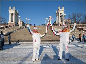 Ttorch bearers Ivan Kosolapov Ivan, left, and Mikhail Malyuga hold their torches during an Olympic torch relay in Volgograd, a city on the Volga River about 500 miles south of Moscow, Russia, Monday, Jan. 20.