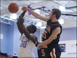 Bowsher High School player Mark Washington (30) has his shot blocked by Elida High School player Austin Allemeier (15).