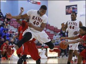 Rogers High School player Fadil Robinson (40) has the ball stripped by Oak Park High School player Orlando Fikes (1).