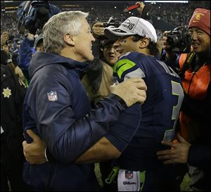 Seahawks coach Pete Carroll celebrates with Russell Wilson after the NFL football NFC championship game on Sunday in Seattle. The Seahawks won 23-17 to advance to Super Bowl XLVIII.