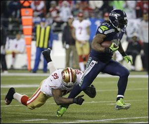 Seahawks running back Marshawn Lynch breaks away from San Francisco 49ers' Aldon Smith for a touchdown run during the second half Sunday in Seattle.