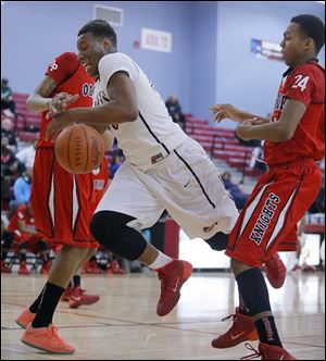 Fadil Robinson of Rogers tries to drive between Oak Park's Kelvon Fuller, left, and Antonio Davis in Monday's MLK Classic at Bowsher.