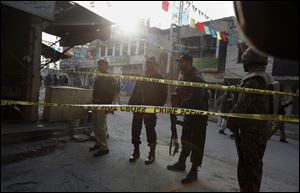 Pakistani police officers and army soldier secure a street close to the site of a suicide bombing in Rawalpindi, Pakistan today.