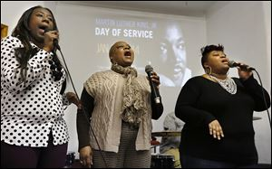 Natasha Campbell, Beatrice Taylor, and Irene Campbell, from left, sing during a Martin Luther King, Jr., Day event at Salem Baptist Church on Vance Street in Toledo.  The service was followed by a meal at the MLK Kitchen for the Poor next door.