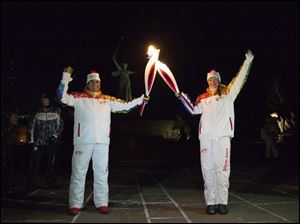 Kamil Larin, left, and Yelena Slesarenko put their torches together during an Olympic torch relay in Volgograd, a city on the Volga River about 500 miles south of Moscow, Russia, Monday with a monument to Motherland at the background.
