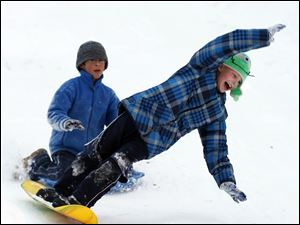 Christian Mays, 8, takes a tumble while sledding as his friend Nathan Davies, 11, watches.