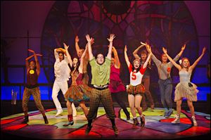 Cast members of 'Godspell' dance and sing during a performance.