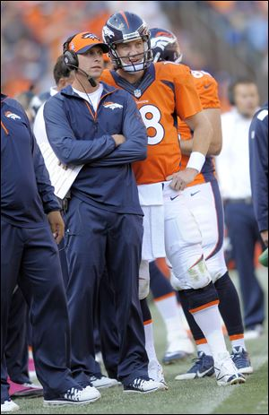 Offensive coordinator Adam Gase, left, has helped Peyton Manning and the Denver Broncos put up gaudy numbers. On Tuesday, Gase withdrew his name from the Browns' head coaching search.