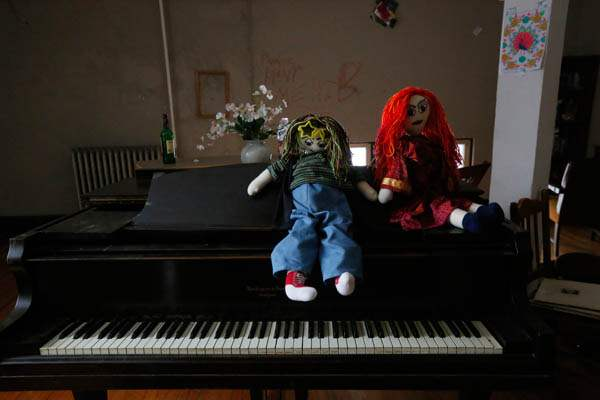 Two-handmade-dolls-sit-on-the-piano-in-one-of-the-c