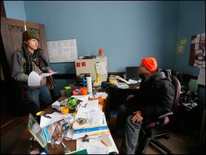 Local artist Kyle Tate talks to Manuel Quintano III, right, in the front office.