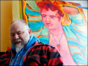 Local artist and resident Greg Tarrant stands in his studio surrounded by his paintings.
