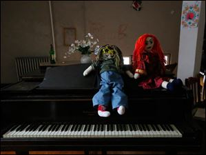 Two handmade dolls sit on the piano in one of the community lounges.