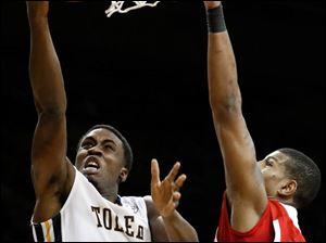 University of Toledo guard Justin Drummond (4) goes to the basket against Northern Illinois forward Darrell Bowie (10).