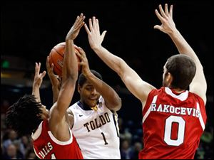 University of Toledo guard Jonathan Williams (1) shoots against Northern Illinois guard Daveon Balls (11) and center Pete Rakocevic (0).