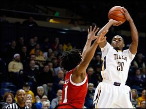 University of Toledo guard Julius Brown (4) shoots against Northern Illinois guard Daveon Balls (11).