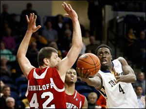University of Toledo guard Justin Drummond (4) goes to the basket against Northern Illinois center Jordan Threloff (42).