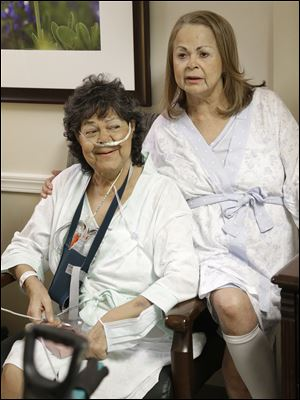 Irma Myers-Santana, left, and her sister Anna Williamson visit in Williamson's hospital room in Houston. Earlier this month the sisters ended up in the same operating room, each getting one lung from the same donor.