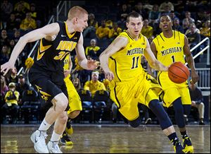 Michigan's Nik Stauskas, right, tries to get around Iowa's Aaron White. The sophomore scored 26 to lead the Wolverines.