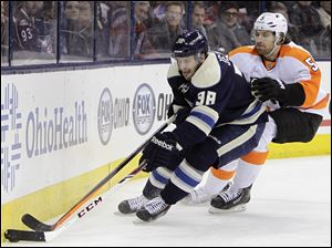 Columbus Blue Jackets' Boone Jenner, left, carries the puck as Philadelphia Flyers' Braydon Coburn defends during the second period of an NHL hockey game, today, in Columbus.