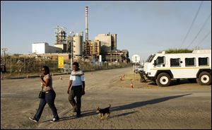 A couple walks with their a dog past the entrance to the Lonmin's platinum mine in Marikana, near Rustenburg, South Africa.