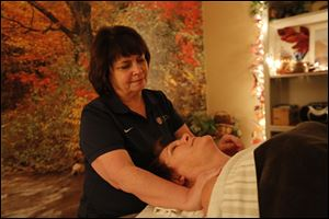 Yvonne Fey, shown massaging Gretchen Mikolajczak of Toledo in her Perrysburg business, moved a step closer to being able to go to an Olympics games.