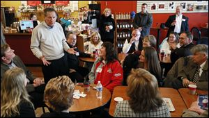 Ohio Governor John Kasich talks with supporters Thursday at Coffee Amici in Findlay.