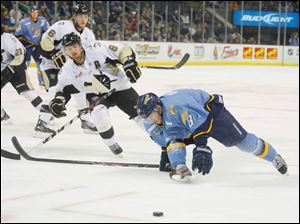 Toledo Walleye player Aaron Clarke (8) tries to get to the puck ahead of  Wheeling Nailers player Barry Goers (8) during the first period.
