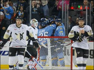 Toledo Walleye players celebrate a goal by Russ Sinkewich (22) against the Wheeling Nailers during the second period.