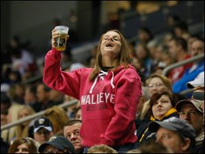 A Toledo Walleye fan cheers the team against the Wheeling Nailers during the first period.