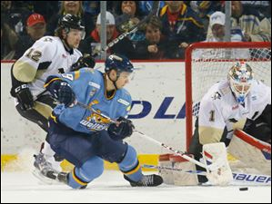 Toledo Walleye player Maxim Shalunov (29) can't get the puck past Wheeling Nailers goalie Mike Condon (1) as Jake Areshenko (12) defends during the second period.