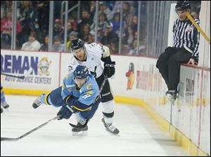 Toledo Walleye player Aaron Clarke (8) passes the puck away from Wheeling Nailers player Jacob Lagace (20) during the first period.