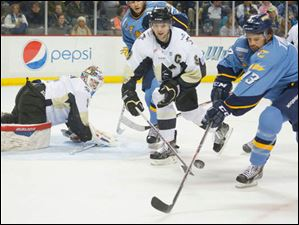 Toledo Walleye player Stephon Thorne (13) tries to handle the rebound against Wheeling Nailers player Dustin Stevenson (9) and goalie Mike Condon (1) during the first period.