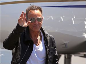 Bruce Springsteen, waves as he arrives at the airport in Cape Town, South Africa, today.