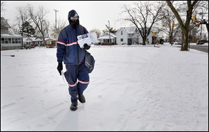 Postal worker Jemael Smith trudges through his rounds in South Toledo. He said, 'It's cold but there's not much you can do about it.' He advised to bundle up and minimize the skin showing to avoid frostbite.