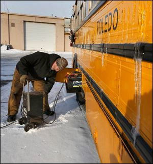 Bert Gilbert of Toledo Public Schools charges bus batteries affected by the cold weather. The weather has forced the district to close repeatedly this year.
