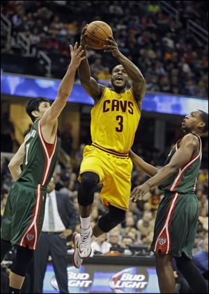 The Cavaliers' Dion Waiters goes up for a shot between Milwaukee Bucks Ersan Ilyasova, left, and Khris Middleton in the second quarter on Friday night in Cleveland.