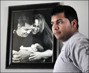 Erick Munoz stands with an undated copy of a photograph of himself, left, with wife Marlise and their son Mateo, in Haltom City, Texas.