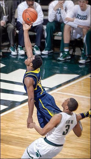 Michigan's Derrick Walton Jr. shoots against Michigan State's Alvin Ellis III.