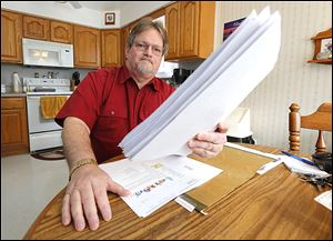 Robert Geis holds a sheaf of job applications in his city home. Mr. Geis, who has been jobless since February, 2013, applies for 15 jobs per week on average.