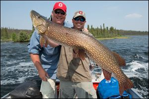 Toledo businessman Don Mewhort, left, with guide Collin Reddekopp, holding a 49-inch northern pike Mr. Mewhort caught in Canada.