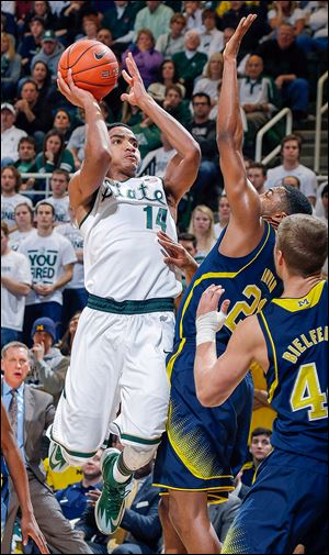 Michigan State's Gary Harris (14) shoots against Michigan's Zak Irvin during the first half. Harris had 27 points for MSU.