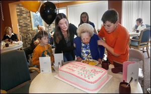 Granddaughter Laura Robinson, second from left, and her children, Ian Robinson, 8, Alaina Robinson, 12,  and Colin Robinson, 14, help Edna Sandys blow out a single candle on her birthday cake during her 105th birthday party at the Elizabeth Scott Community in Maumee.
