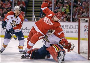 Detroit Red Wings right wing Daniel Cleary (71) falls over Florida Panthers goalie Tim Thomas (34) during the first period of an NHL hockey game in Detroit, Sunday, Jan. 26, 2014. (AP Photo/