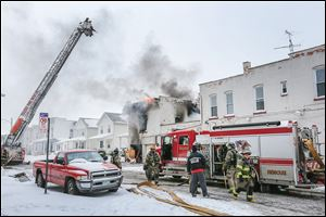 Toledo firefighters battle the blaze at 528 Magnolia, a six-unit apartment building in North Toledo. Two firefighters died from injuries while fighting the blaze that was reported Sunday afternoon.