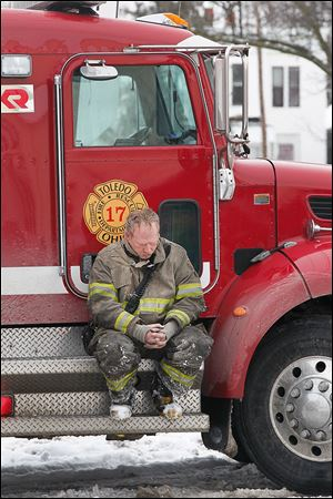 A Toledo firefighter waits outside of 528 Magnolia St. where a blaze consumed an apartment building and claimed the lives of two firefighters.